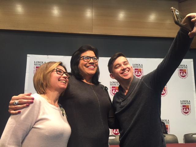 Two women and a man side by side taking a selfie.