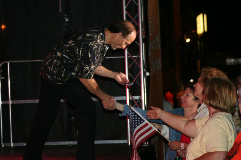 Singer Lee Greenwood bending down to accept a button from military mom Sharon McCauley