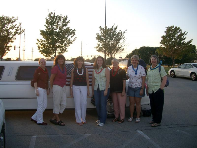 Sharon McCauley center with six other women in front of a white limousine
