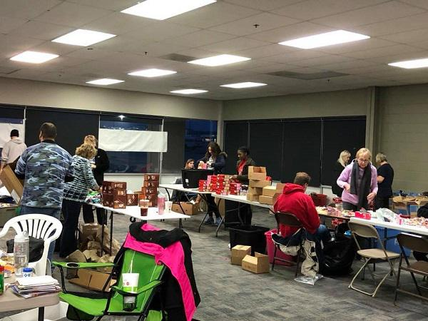 A room of volunteers stuff candy and other items into homemade stockings for soldiers around the globe