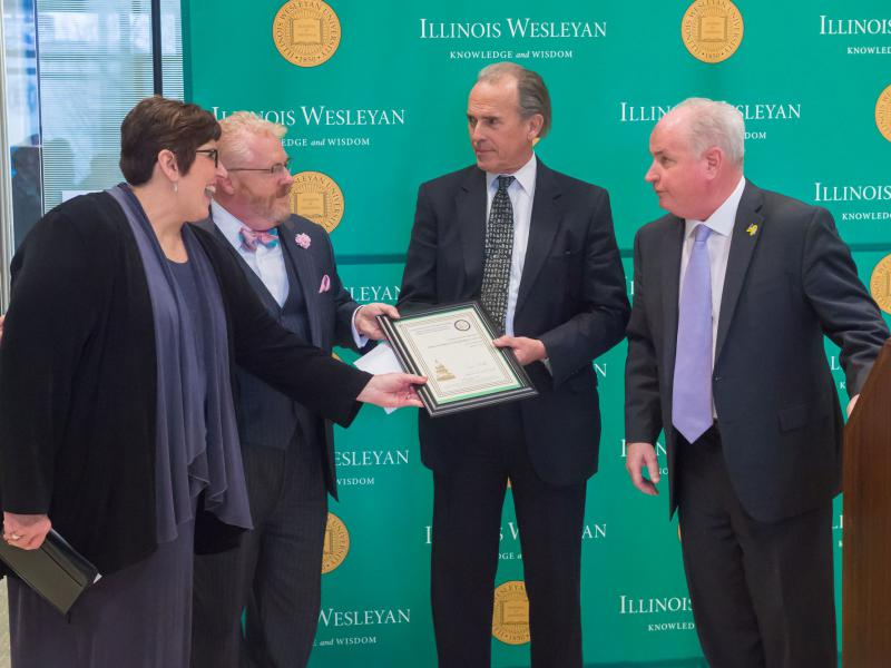Director Karen Bussone (far left) and Illinois Wesleyan Provost Jonathan Green receive a proclamation from state Reps. Keith Sommer and Dan Brady (far right) at an event launching the McLean County Small Business Development Center in March.