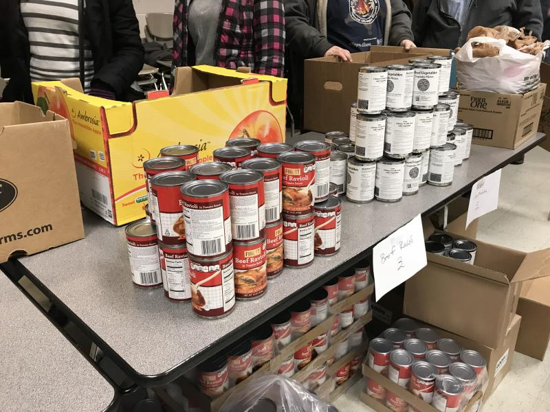 Volunteers stack canned goods for food bank participants at the Eastern Illinois Foodbank distribution at Normal Community West High School on Dec. 16, 2017.