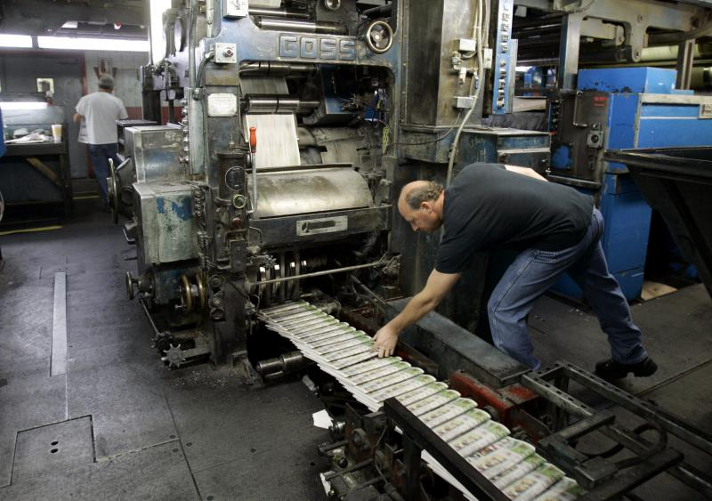 A pressman grabs a freshly printed St. Louis Post-Dispatch paper off the press at the St. Louis Post-Dispatch's printing facility in Maryland Heights, Missouri, in 2008.