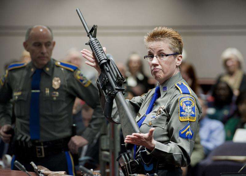 Detective Barbara J. Mattson of the Connecticut State Police holds up a Bushmaster AR-15 rifle, the same make and model of gun used by Adam Lanza in the Sandy Hook School shooting.