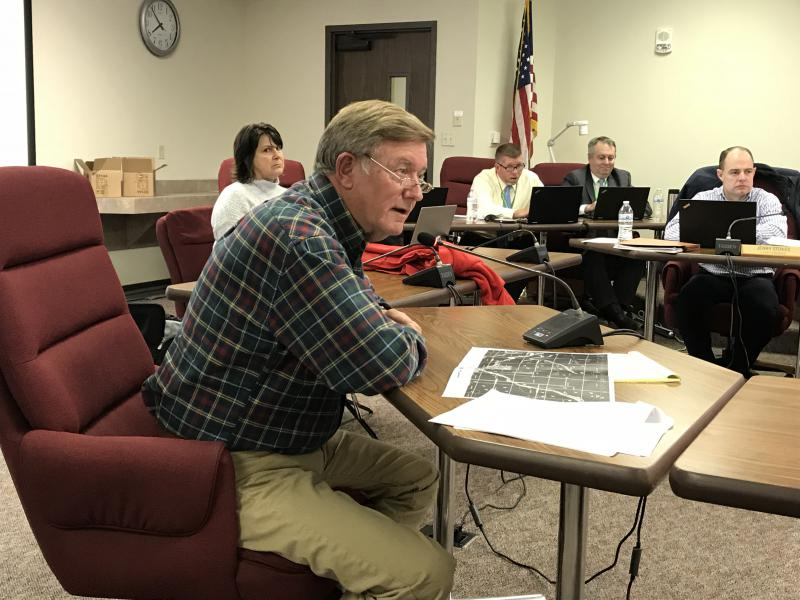 Jim Pitzer of Colfax grills Invenergy representatives about Illinois Department of Natural Resources standards on wind tower placement Tuesday night.