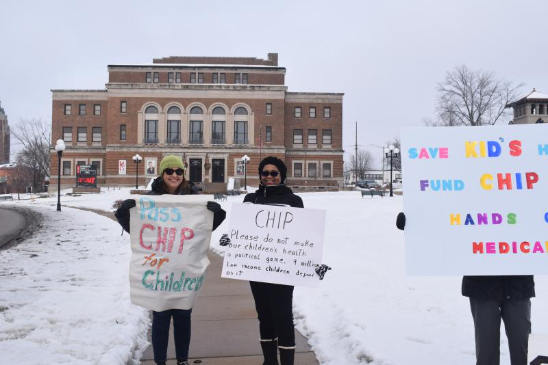 Jodie Slothower of the activist group Voices of Reason, left, and Normal Township Trustee Arlene Hosea were among those protesting the potential end of the CHIP progam that insures thousands of Illinois children.