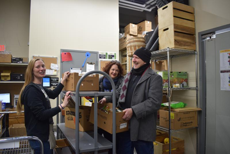 Beacon of Hope volunteers Jo Ellen Scott and Gary Calhoon, left, receive a box of apples from a Green Top Grocery manager to give away at the West Bloomington Revitalization Project offices.