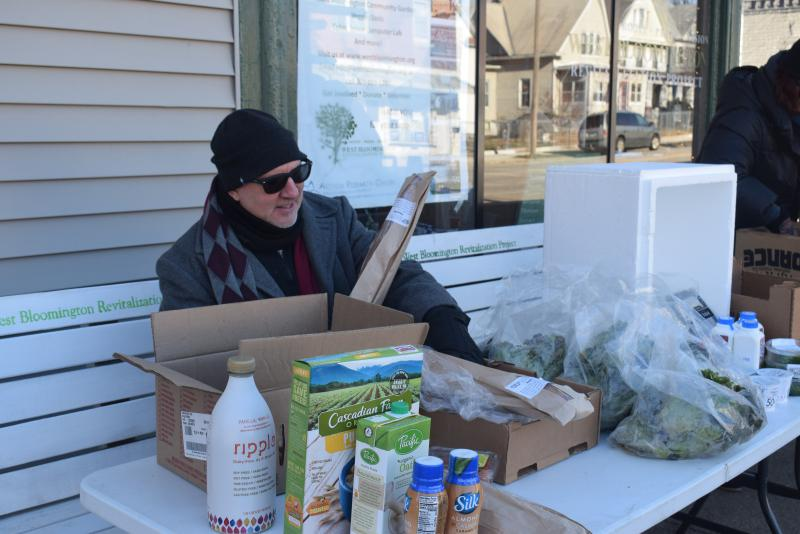 Beacon of Hope volunteer Gary Calhoon looks over some of the food donated by Green Top Grocery for a Saturday morning food giveaway. Supermarkets donate items that are slightly past their sell-by dates.