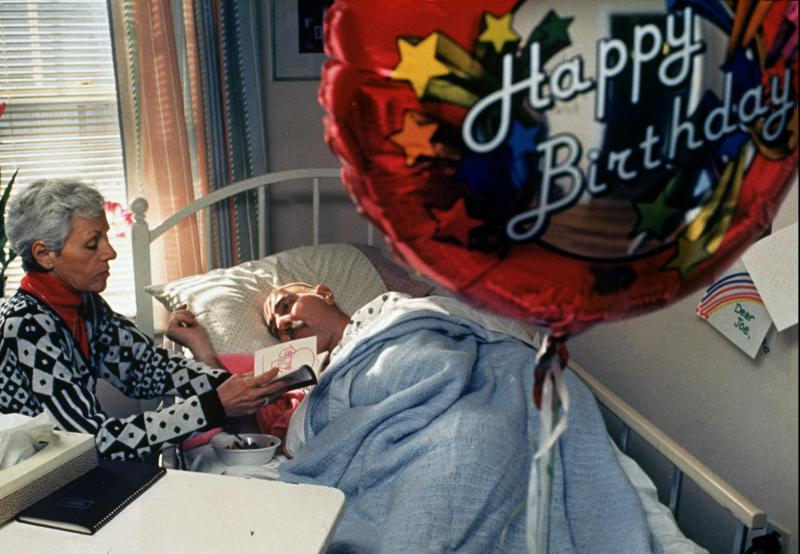 A hospice patient in Cambridge, MA listens as his sister reads to him.