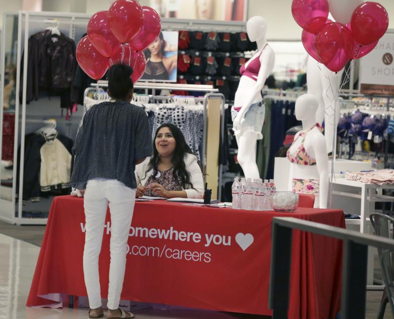 Target human resources representative Critsina Lugo, seated, talks with a job seeker at a Target store in Dallas.