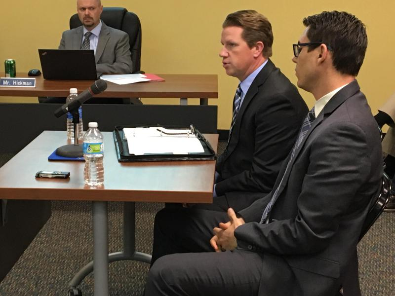 Two men sit at a table and address the Unit Five School Board. They are Economic Development Council Director Kyle Ham and Rivian Automotive CEO RJ Scaringe