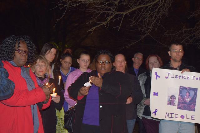 A group of women and a couple of men with candles and a sign at a vigil for a slain domestic violence victim .
