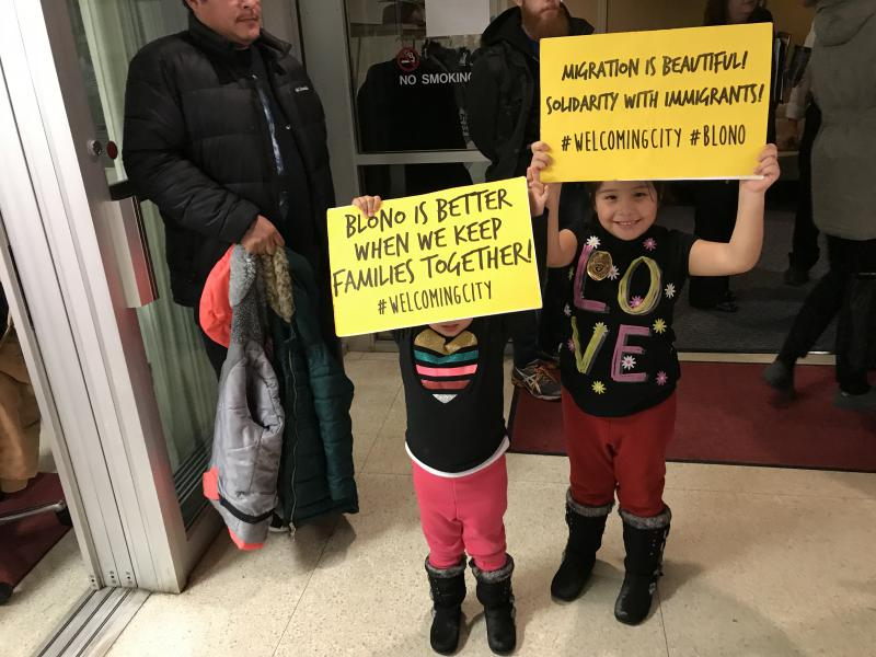 Two young girls hold signs in support of the Welcoming City ordinace at Monday's Bloomington City Council meeting.