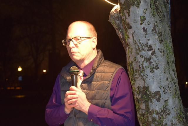 Man standing against a tree holding a microphone to deliver short remarks at a vigil.