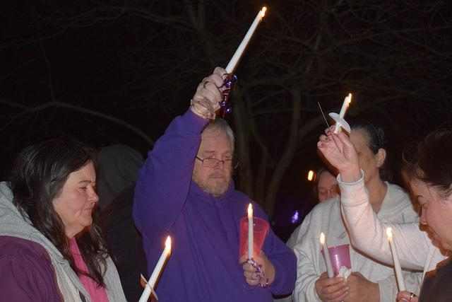 Man holding candle high above his head, surrounded by others with candles lit by its initial flames.