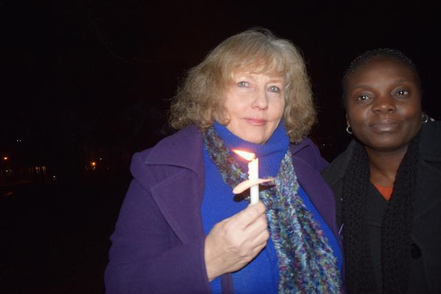 Two women side by side with one holding a candle at a vigil in a park for a slain woman allegedly killed by her husband in Bloomington.