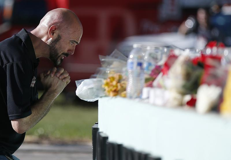 Kevin Siegelbaum, a special education teacher at Marjory Stoneman Douglas High School, leans in to pray Thursday, Feb. 15, 2018, in Parkland, Fla., during a community vigil.