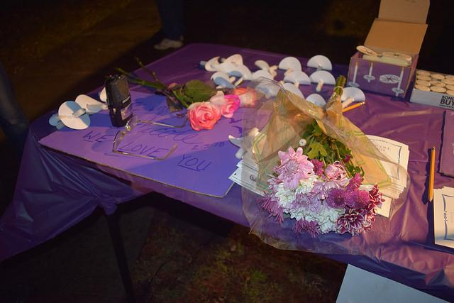 Flower, candles and signs on a table.