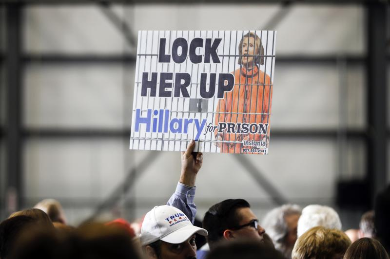 """An attendee holds a """"LOCK HER UP"""" sign before the arrival of Republican presidential candidate Donald Trump at a campaign rally, Friday, Nov. 4, 2016, in Wilmington, Ohio."""
