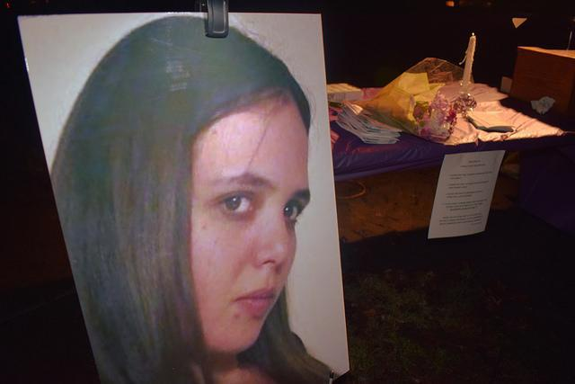 A large photo of a 30 year-old mother allegedly killed by her husband with flowers and candles in the background.