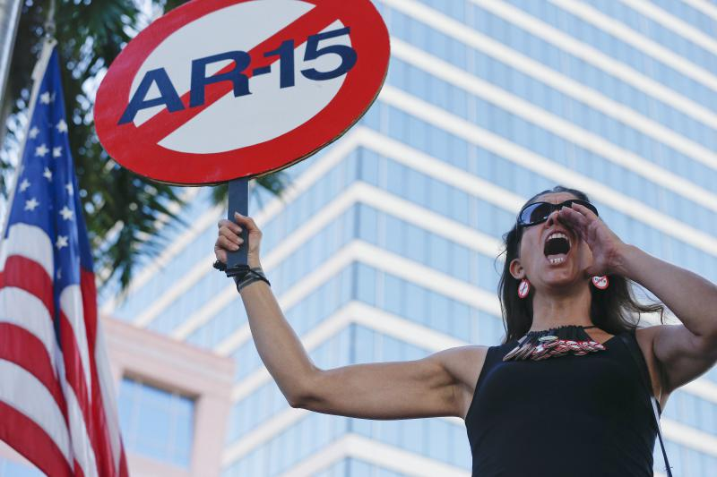 "Alessandra Mondolfi holds a sign against AR-15 weapons as she yells, ""No More"" during a protest against guns on the steps of the Broward County Federal courthouse in Fort Lauderdale, Fla., on Saturday, Feb. 17, 2018."