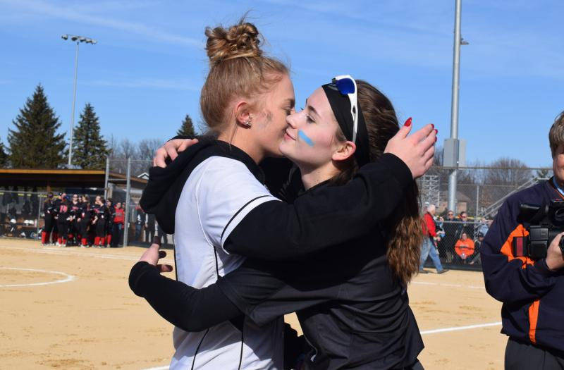 Ellie Sonetz, whose sister Olivia died in a car crash last week, gets a hug from one of her sister's teammates on the Normal West high school softball team.