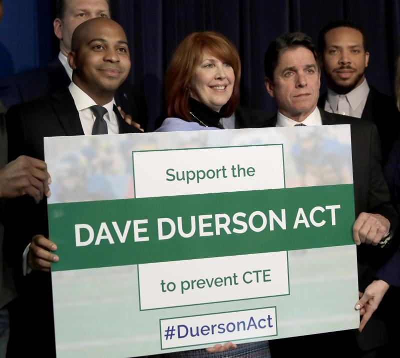 From left, Tregg Duerson, Illinois state Rep. Carol Sente, D-Vernon Hills, and former Chicago Bears' Mike Adamle pose for a photo after a news conference in support of the Dave Duerson Act to Prevent CTE on Thursday, Jan. 25, 2018, in Chicago.