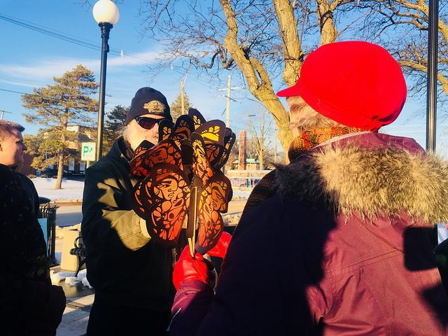Man receives a large butterfly on a stick from a woman at a rally to support a Welcoming City ordinance in Bloomington.