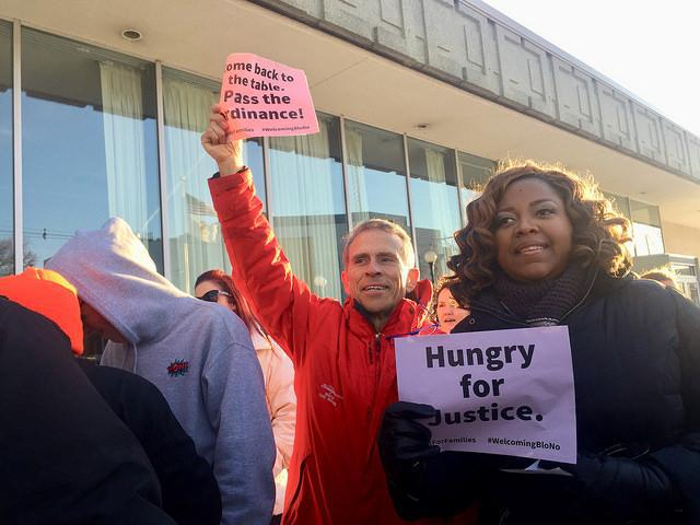 Man raising sign over his head next to woman clutching sign to her chest.