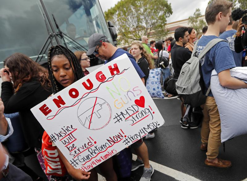Tyra Hemans, 19, left, and Logan Locke, 17, right, students who survived the shooting at Stoneman Douglas High School, wait to board buses in Parkland, Fla., Tuesday, Feb. 20, 2018.