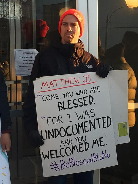 Man holding a sign that puts a twist on a Bible verse.