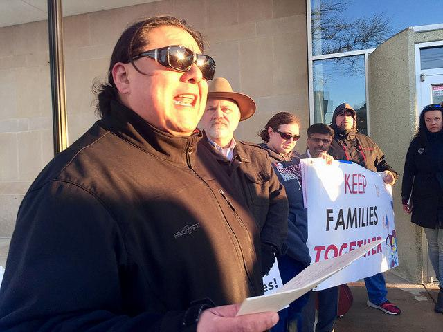Man wearing sunglasses holding a script delivers a fiery speech outside Bloomington City Hall.