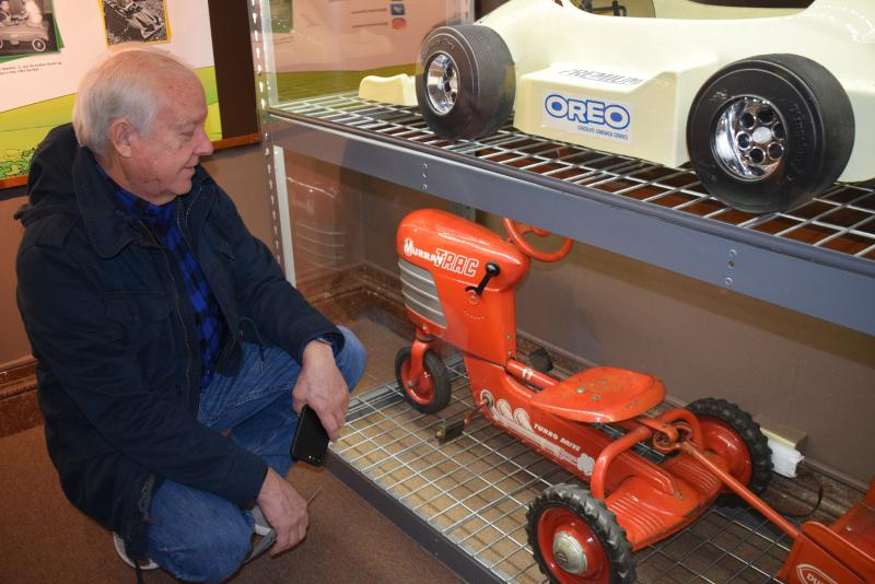 Man bending down to look at a mini model of a riding tractor