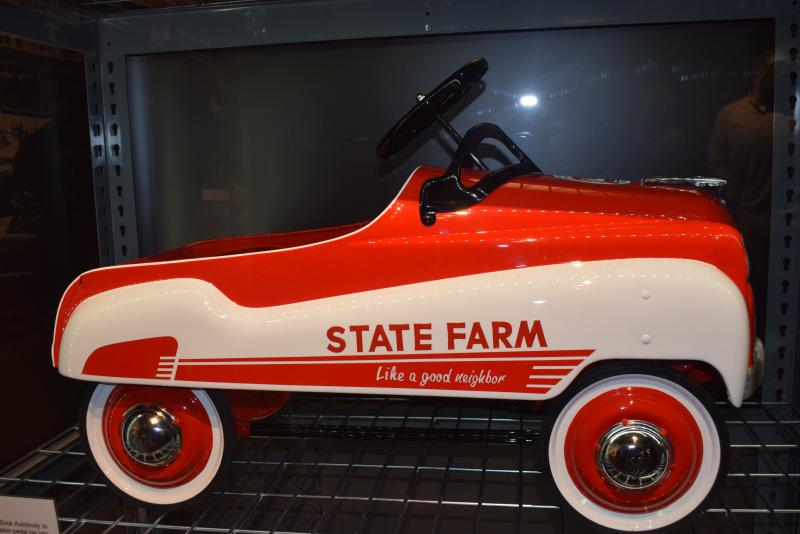 A minature pedal car from the 1950s with the the State Farm red and white colors and logo.