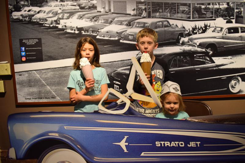 A brother, sister and toddler girl behind a cut-out of a vintage car with shakes and a bell hop hat.