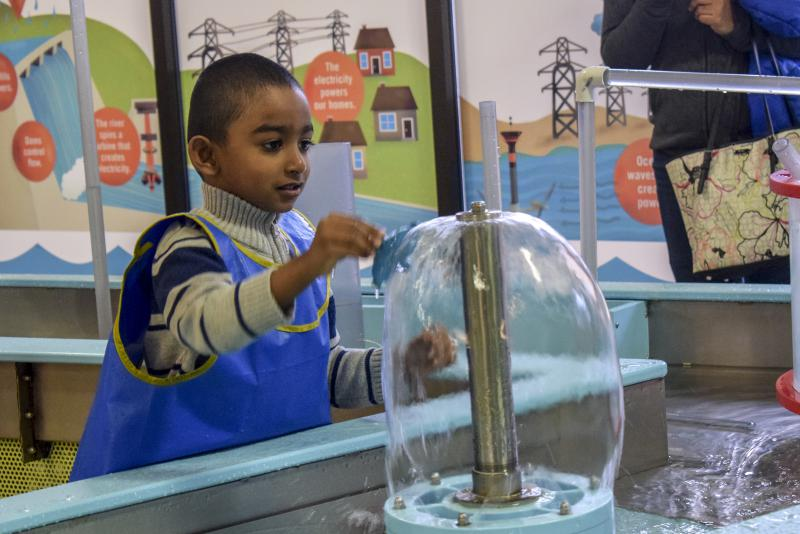 A visitor plays at the water table at the Children's Discovery Museum in Uptown Normal.