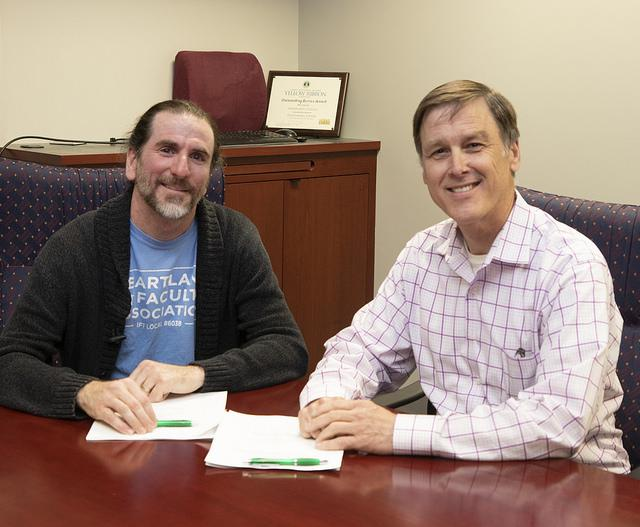 :  Faculty Association Lead Sean Colcleasure and Board Chair Gregg Chadwick sign the new 3-year agreement.