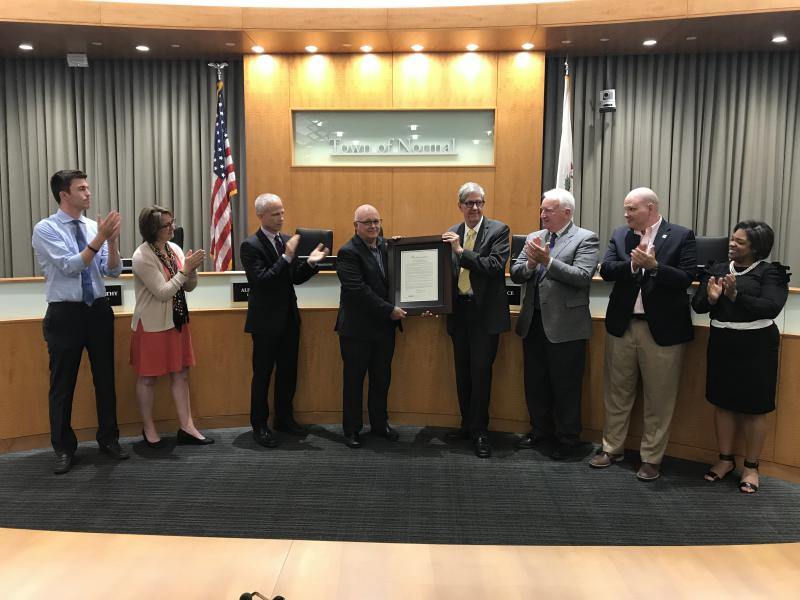 Retiring City Engineer Gene Brown (center left) receives the congratulations of the Normal Council for his decades of service.