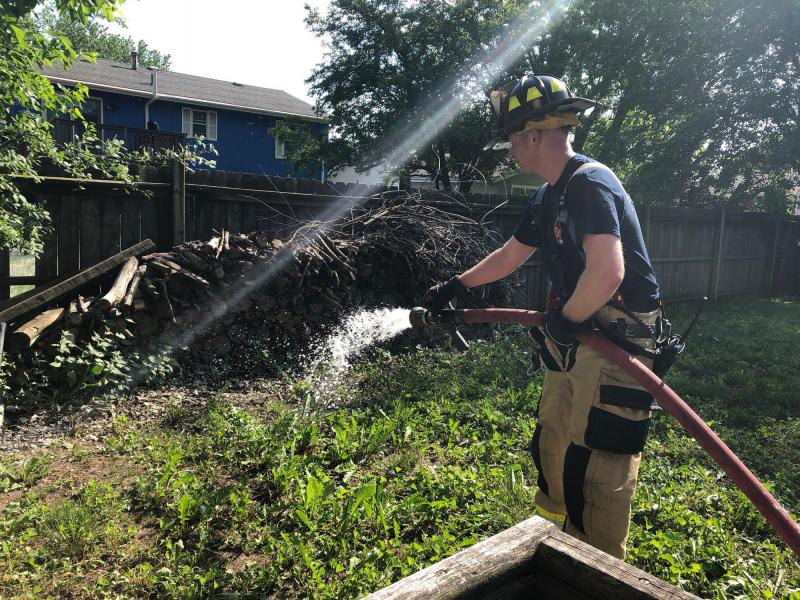 Firefighter sprays water on a wood pile.