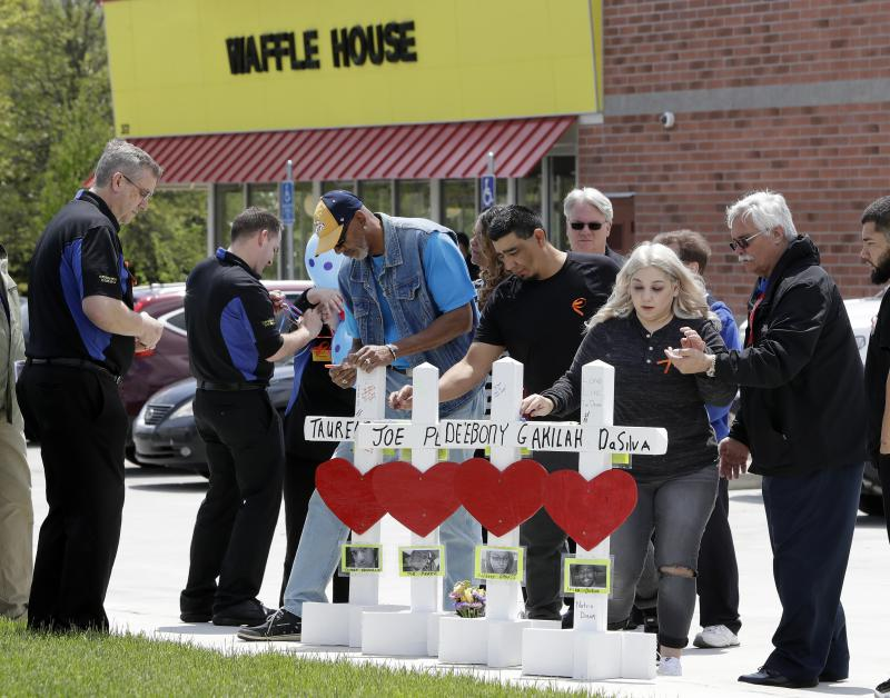 Family members of people killed at a Waffle House restaurant write messages on wooden crosses set up as a memorial Wednesday, April 25, 2018, in Nashville, Tenn.