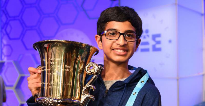 A picture of a boy with a spelling bee trophy