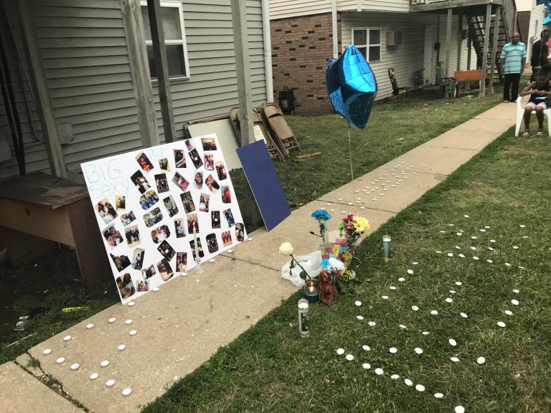 Candles and photos mark a memorial for one of the victims of the June 10th shootings of four people on Orchard Road in Bloomington.
