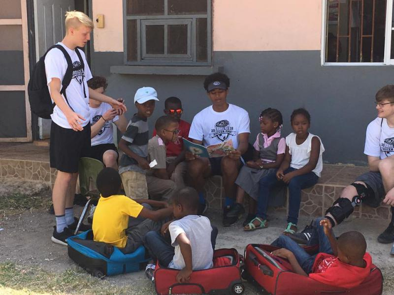 Normal West boys soccer player Jordan Walker reads to kids in Jamaica during their recent soccer-and-service trip.