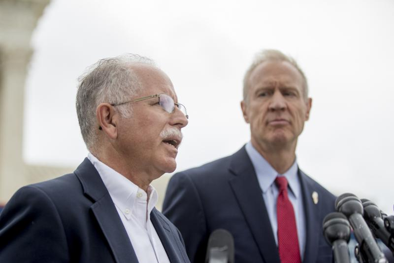 Plaintiff Mark Janus, left, accompanied by Gov. Bruce Rauner, right, speaks outside the Supreme Court after the court rules in a setback for organized labor that states can't force government workers to pay union fees, June 27, 2018, in D.C.