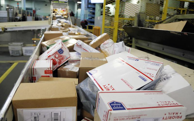 Packages travel on a conveyor belt for sorting at the main post office in Omaha, Neb., in 2017.