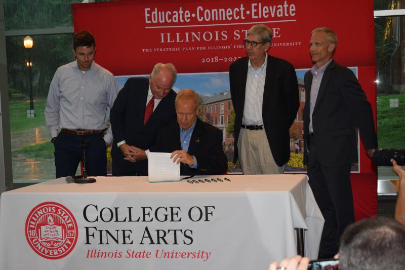 Gov. Bruce Rauner signs House Bill 1910 at Illinois State University's Center for Performing Arts on Thursday, June 21, 2018.