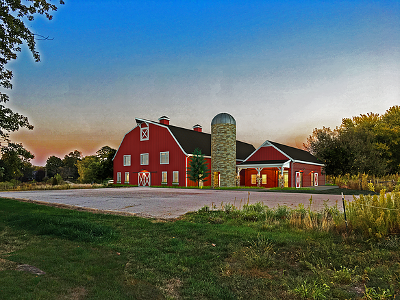 Exterior of a barn and a silo with a parking area in front.