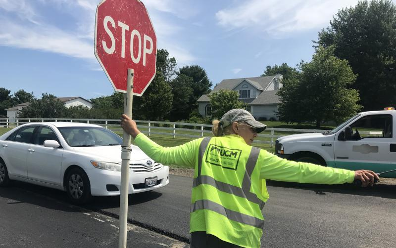 Becky Slightom of Bloomington on the job Friday, July 6, 2018, during a resurfacing project on Oakland Avenue in Bloomington Township.