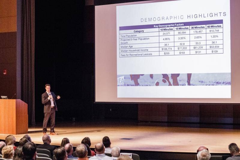 Evan speaks on stage with presentation behind him