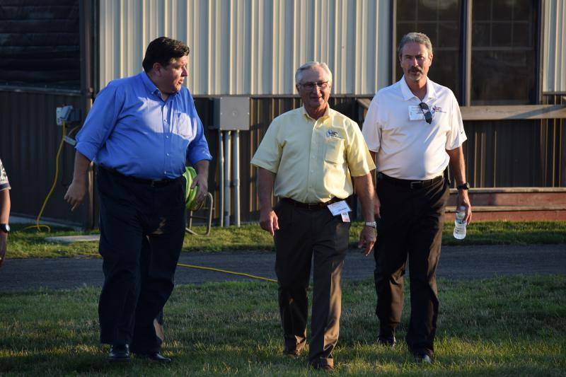 JB Pritzker walks at a farm